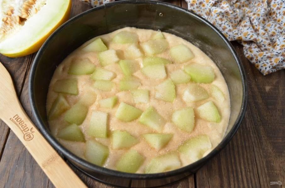 Форму застелите пергаментом, перелейте в неё тесто. Уложите кусочки дыни сверху. Смешайте ванильный сахар с четвертью чайной ложки молотой корицы, посыпьте сверху. Отправьте в духовку на 30 минут, температура — 180 градусов.