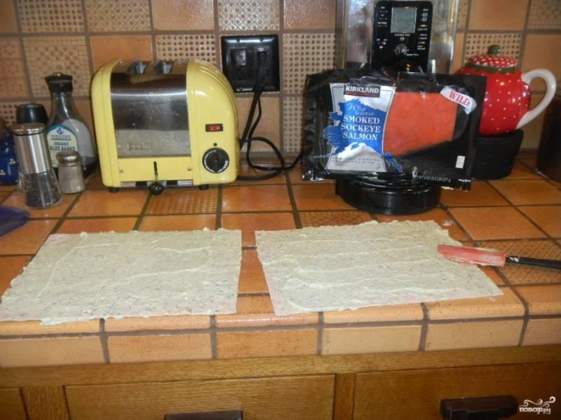 Подготовьте два лаваша, смажьте их плавленым сыром. Можете добавить в сыр измельченную зелень по желанию.