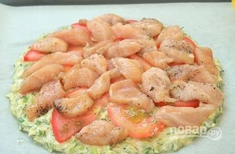 На помидоры выкладываем кусочки куриного филе, посыпаем все молотым перцем.