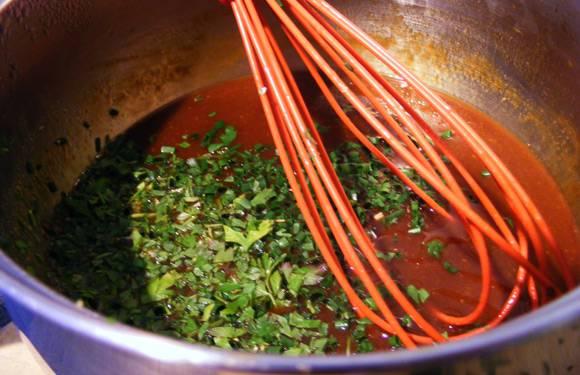 2. Теперь можно заняться соусом. В небольшой сотейник налить немного растительного масла и разогреть. Очистить чеснок, измельчить и обжарить пару минут. Влить примерно половину томатного соуса, добавить соль, перец, горчицу и немного винного уксуса. Как следует перемешать и уварить соус до загустения. Сняв сотейник с огня, всыпать горстью свежей зелени.