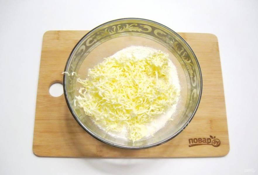 Холодное масло натрите на терке прямо в миску с мукой и сахаром. Перемешайте до состояния крошки.