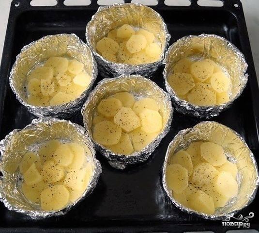 Формочки из фольги переложите на противень и смажьте маслом. Картофель помойте, почистите и нарежьте кружками. Разложите его по формам. Посолите и поперчите картофель.