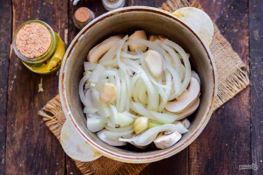 Переложите грибы в кастрюлю с толстыми стенками. Очистите лук, нарежьте полукольцами, добавьте к грибам. Также добавьте зубчики чеснока.