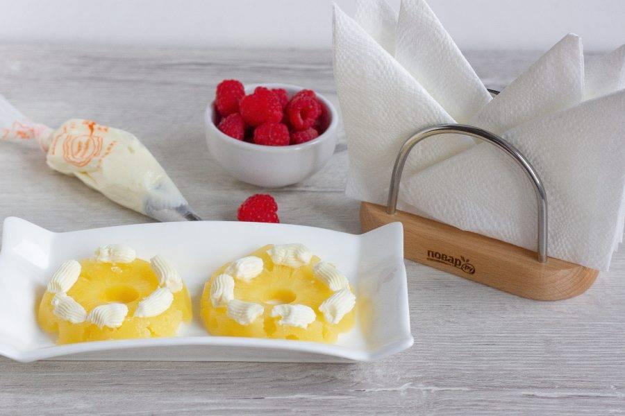 На кольца ананаса выложите сыр. Я это делала в помощью кондитерского мешка и насадки. Можно воспользоваться чайной ложкой.