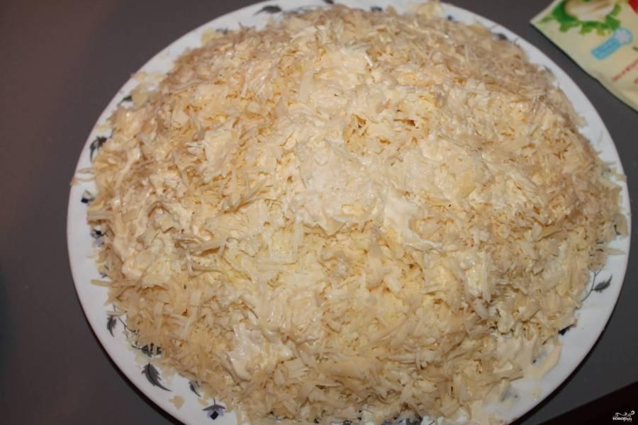 Отварные яйца натрите на мелкой терке. Один желток отложите для украшения салата. Раскрошенными яйцами выкладываем следующий слой салата. Снова смазываем майонезом и присыпаем тертым сыром.