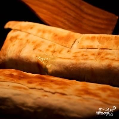 Прогреваем свернутые лаваши на слабом огне под крышкой, примерно по 3-4 минуты с каждой стороны. Нам нужно, чтобы лаваш слегка подрумянился, а сыр в начинке стал плавиться.