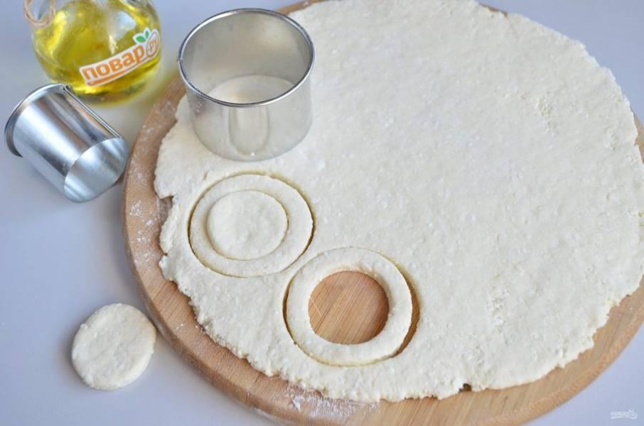 4. Замесите тесто, раскатайте его толщиной в 1 см, с помощью вырубок разных диаметров вырезайте калачи.