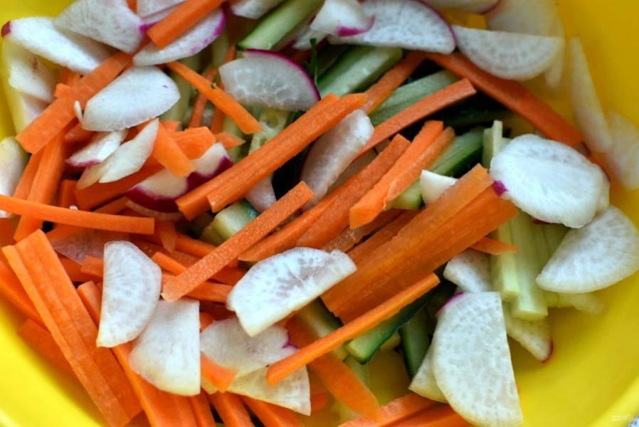 Овощи очистите, промойте и обсушите. Нарежьте вручную соломкой огурцы и морковь, тонкими кружочками – редис. Выложите в глубокую миску, слегка присолите и  посыпьте черным перцем.