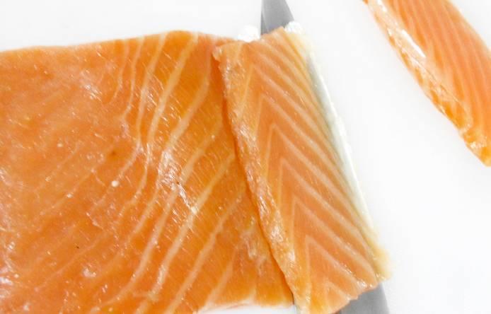 Филе копченого лосося нарезаем тонкими пластинками.