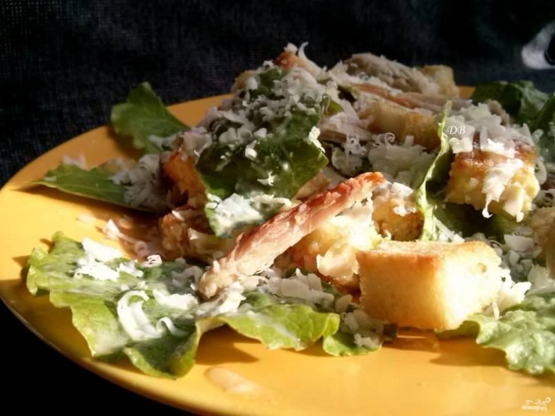 Листья салата промойте, обсушите и порвите на крупные куски. Добавьте крутоны, 40 г. тертого пармезана и заправку, перемешайте. Выложите салат на тарелки, добавьте кусочки курицы. посыпьте сверху оставшимся пармезаном. Приятного аппетита!