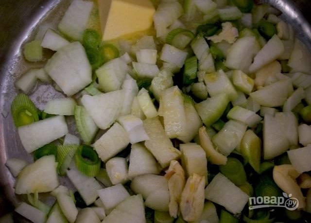2.Нарежьте репчатый лук кубиками, измельчите порей и чеснок. Разогрейте кастрюлю со сливочным маслом, выложите чеснок, лук, порей, обжаривайте до мягкости.