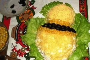 Далее начинаем украшать салат. Шею пчелки выкладываем из кукурузы и маслин в 2 слоя.