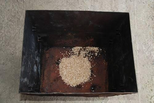 3. На дно коптильни насыпать пару жмень опилок, лучше всего из твердых пород деревьев (дуб, бук, ольха) или фруктовых деревьев.
