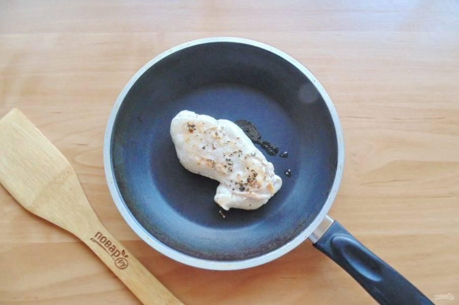 Куриную грудку посолите и поперчите по вкусу. Выложите в сковороду с маслом и обжарьте с обеих сторон до легкой золотистой корочки в течение 4-5 минут.