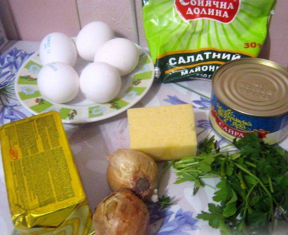 1. Подготовим ингредиенты. Рыбу достаем из масла и чуть разминаем вилкой, сыр отправим в морозилку, лук и зелень чистим и моем.