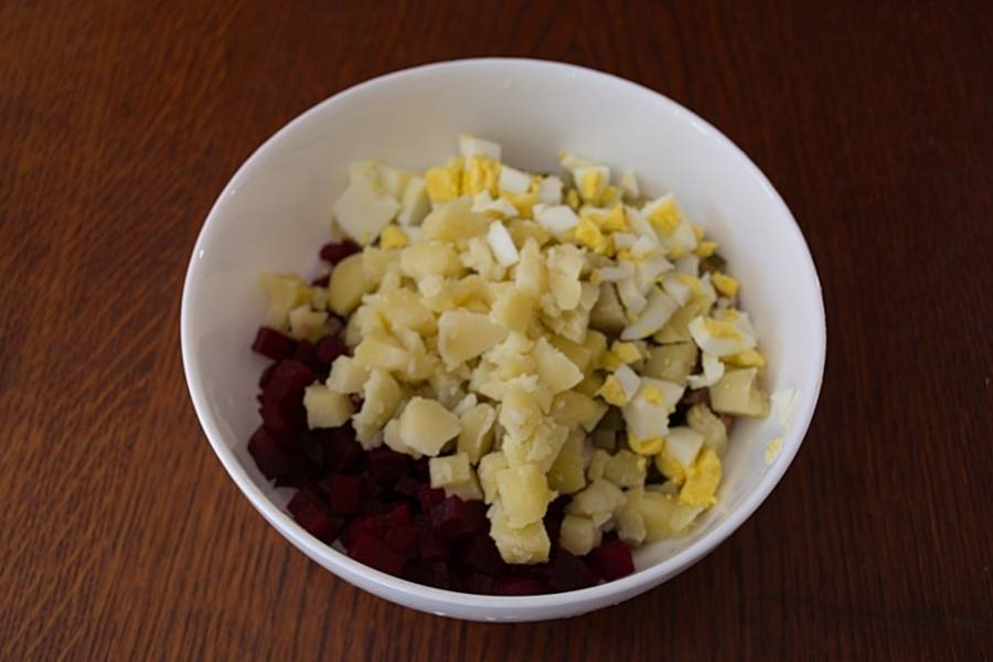 В едином салатнике соединяем нарезанные продукты: свеклу, огурцы, отварной язык. Добавляем измельченные отварной картофель и яйцо. Заправляем все сметаной.