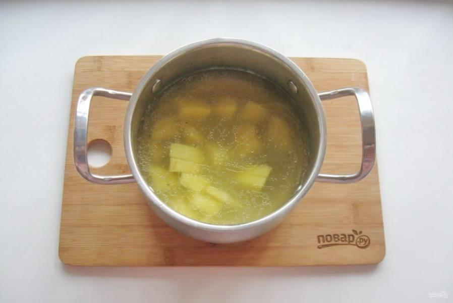 Картофель очистите, помойте и нарежьте кубиками, выложите в кастрюлю и начинайте варить суп.