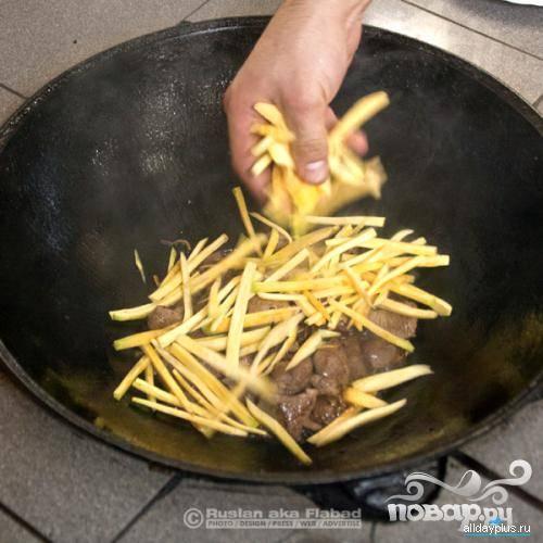 Когда мясо немного обжарится, начинаем выкладывать морковку - поэтапно.