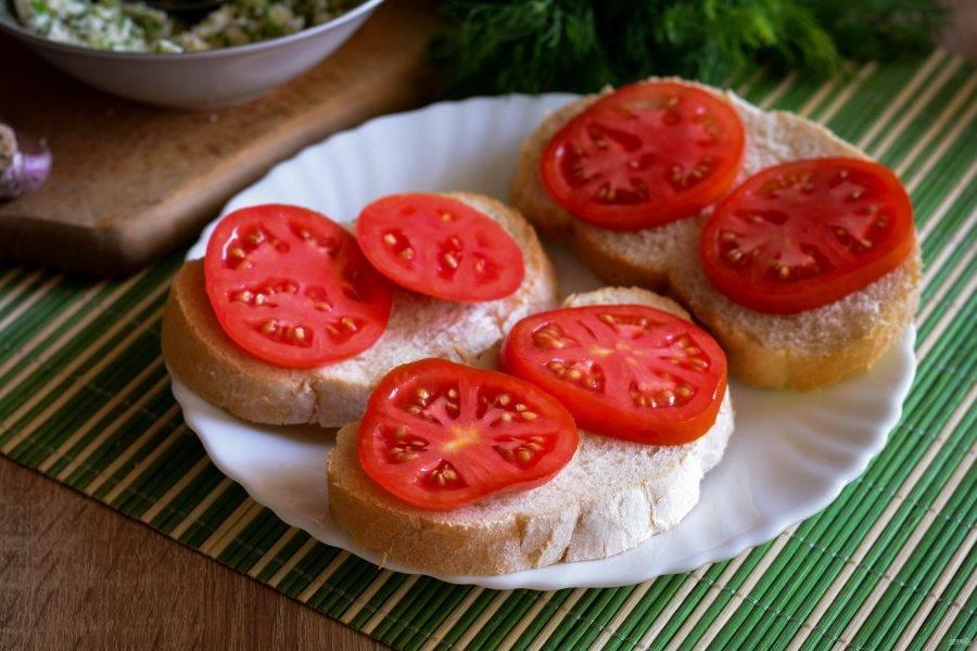 На ломтики хлеба выложите кружочки помидора.
