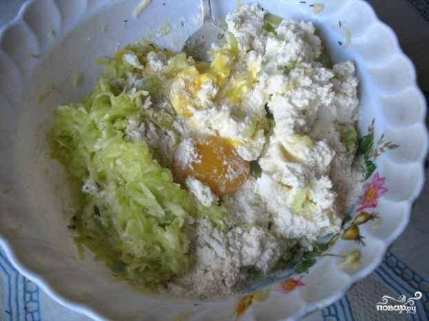 Затем в глубокую миску добавить творог, отжатые от сока кабачки, яйца, муку и зелень.