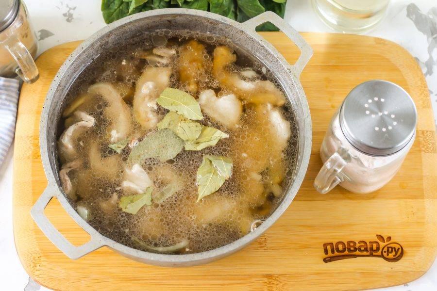 Затем влейте горячую воду, убавьте нагрев до среднего и выложите лавровые листья. Посолите и тушите хрящи не менее 1 часа.