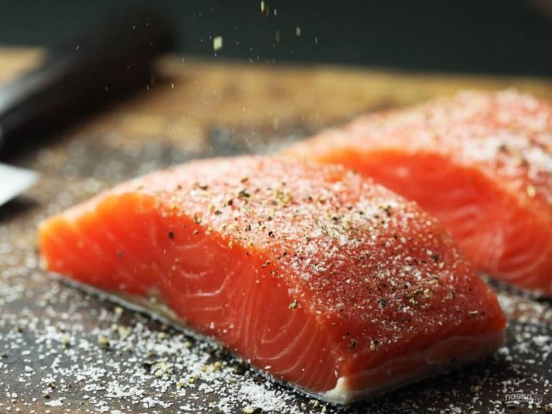 2.Выложите рыбу на разделочную доску, посыпьте солью и черным молотым перцем.
