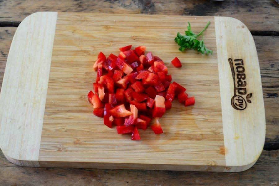 Сладкий перец порежьте кубиком и отправьте следом в кастрюлю.