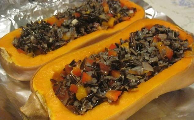 Выложите начинку из риса и овощей в половинки тыквы. Залейте вином и бульоном.  Сверху положите веточки тимьяна и сливочное масло кусочками. Закройте фольгой, отправьте в духовку минут на 30. За 5-10 минут до готовности снимите фольгу и еще немного присыпьте тертым сыром.