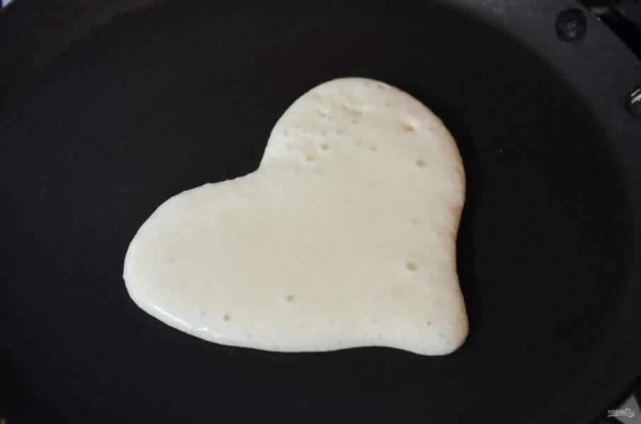 5. Смажьте блинную сковороду капелькой масла, разогрейте. В кондитерский мешок перелейте часть теста. Рисуйте сердечки!