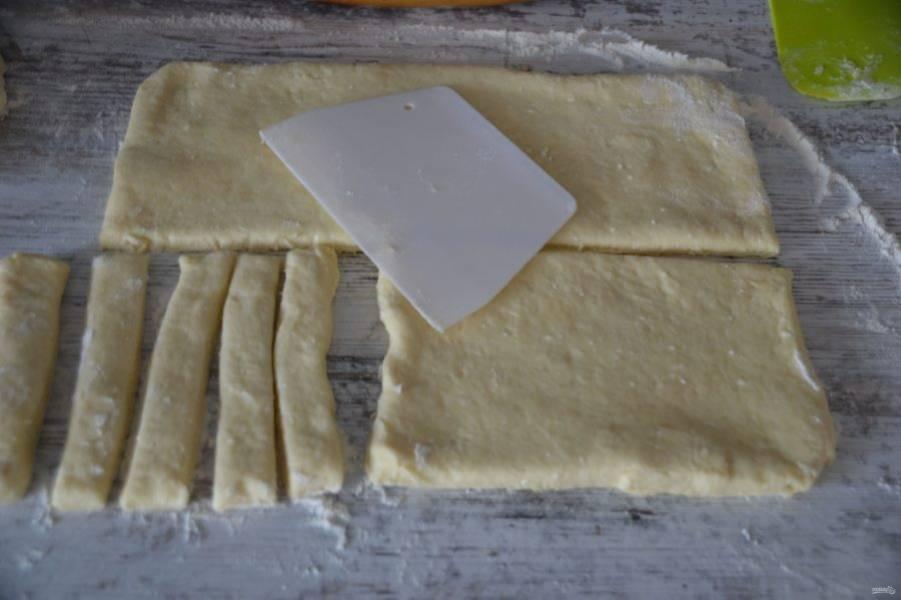 Припылите рабочую поверхность стола мукой, выложите тесто, разровняйте его в пласт толщиной 0.7-0.8 см. Нарежьте палочки из теста.