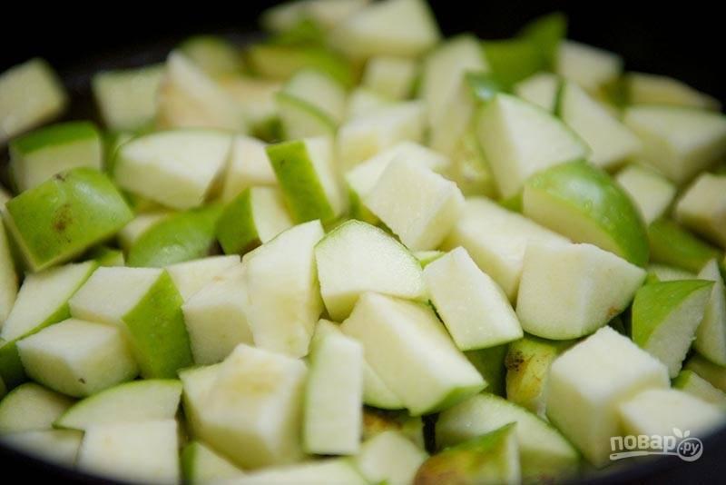 4. Яблоки вымойте, обсушите, удалите сердцевину и нарежьте мелкими кубиками. Выложите в сотейник со сливочным маслом. Оставьте тушиться на медленном огне. В процессе подливайте водичку по необходимости.