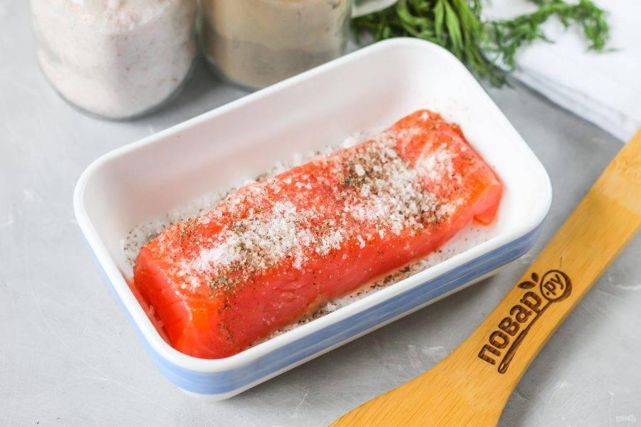 Кусочек красной рыбы с кожей промойте в воде. Если в нем есть длинные кости, то извлеките их с помощью пинцета. Выложите кусочек в глубокую емкость, присыпьте солью и молотым черным перцем. По желанию добавьте сахарный песок. Он придаст мякоти легкую сладость, но можно обойтись и без него. Свежую зелень не добавляйте — она закислит закуску и испортит ее вкус.