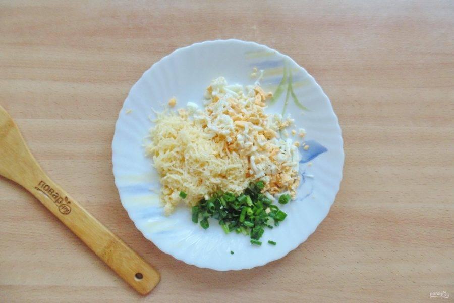 Яйца сварите вкрутую, охладите и очистите. Натрите на терке яйца и твердый сыр. Зеленый лук мелко нарежьте.