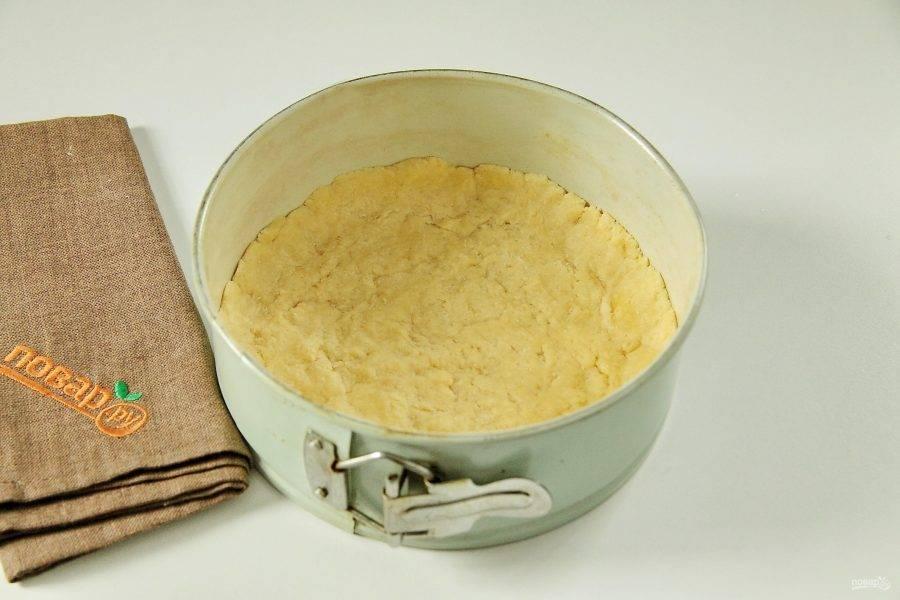 6. Форму для выпечки смажьте маслом и руками распределите в нем тесто, формируя небольшие бортики.