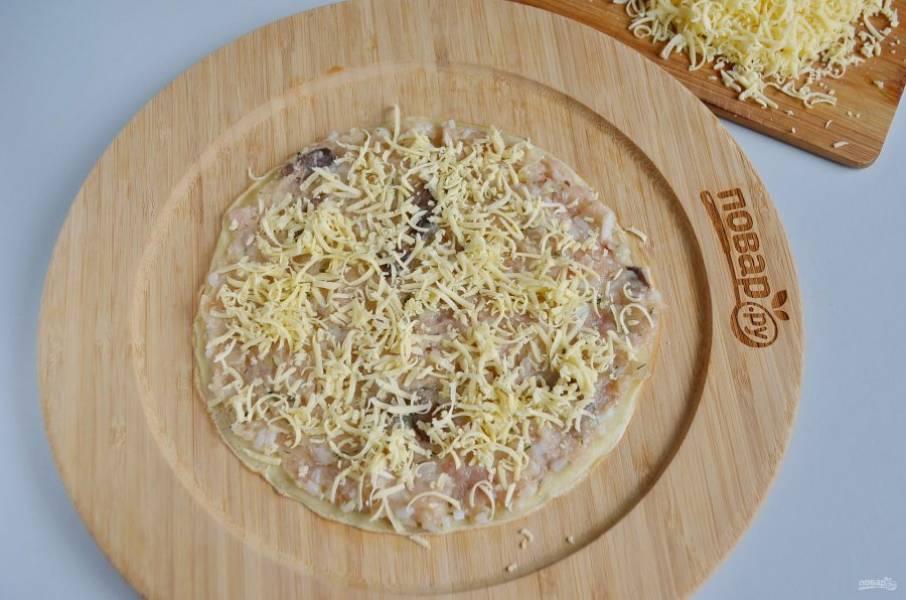 Полученный фарш нанесите на блины, толщина фарша не более 1 см. Сверху посыпьте тертым сыром.