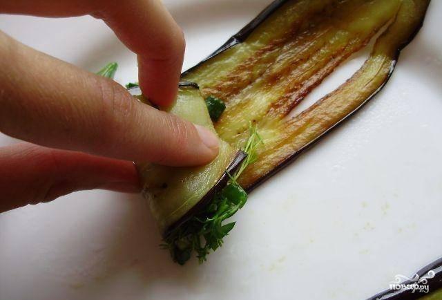 Теперь главное - берем обжаренные баклажаны, кладем на краешек немного начинки из чеснока и зелени и заворачиваем в рулетик - так, как показано на фото.