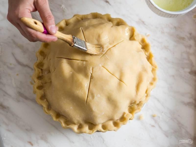 Накрываем яблоки вторым слоем теста, отрезаем лишнее, делаем надрезы сверху и смазываем поверхность пирога взбитыми яйцами.