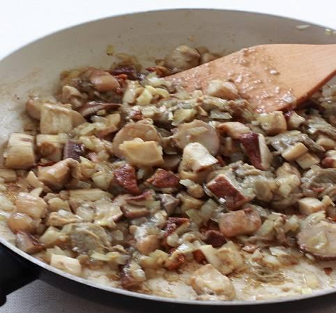 3. На отдельной сковороде разогреть немного масла и отправить туда лук. Когда он станет прозрачным и мягким можно добавить вымытые и нарезанные грибы. В данном случае используются белые грибы, но при желании их можно заменить любыми другими или совершенно исключить.
