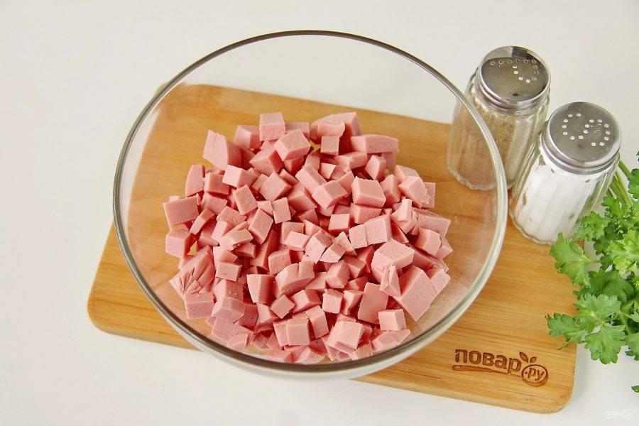 Колбасу нарежьте небольшими кубиками и переложите в глубокий салатник.