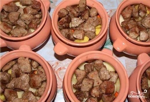 Посолите и поперчите овощи в горшочках, выложите на них мясо. Если у вас есть приправы для мяса или картофеля, их тоже можно добавить. Разогрейте до ста девяноста градусов духовку и запекайте мясо в горшочках сорок минут. Пока блюдо еще горячее, положите в каждый горшочек, по желанию, кусочек сливочного масла.