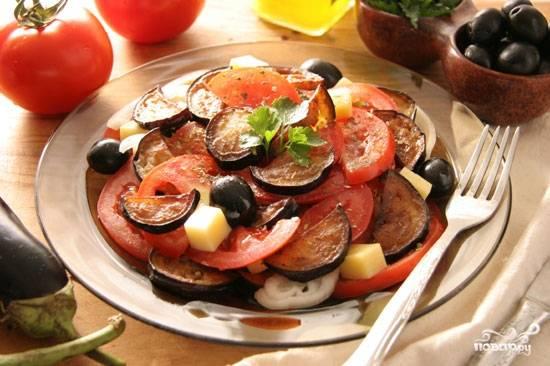 Теперь уложим помидоры и баклажаны слоями на плоскую тарелку, пересыпая маслинами и перекладывая кольцами лука. Каждый слой сбрызнем заправкой.  Сверху выложим кубики сыра и посыплем зеленью.  Приятного аппетита!