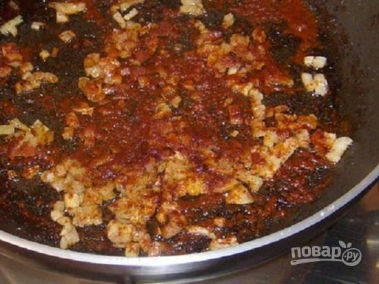 Очистим и мелко нарежем репчатый лук, обжарим его на сковороде, в которой обжаривались ребрышки. Когда лук подрумянится, добавим на сковороду паприку и томатную пасту. Обжариваем буквально минуту.