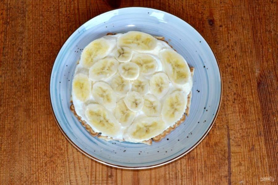 Выложите нарезанные ломтиками бананы.
