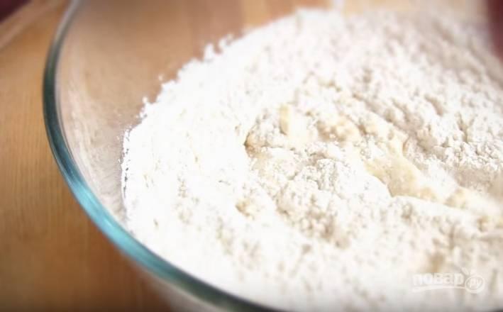 2. Просейте в миску муку. Вымесите руками мягкое, эластичное тесто, которое не липнет к рукам. Оставьте тесто в миске в теплом месте минут на 40.