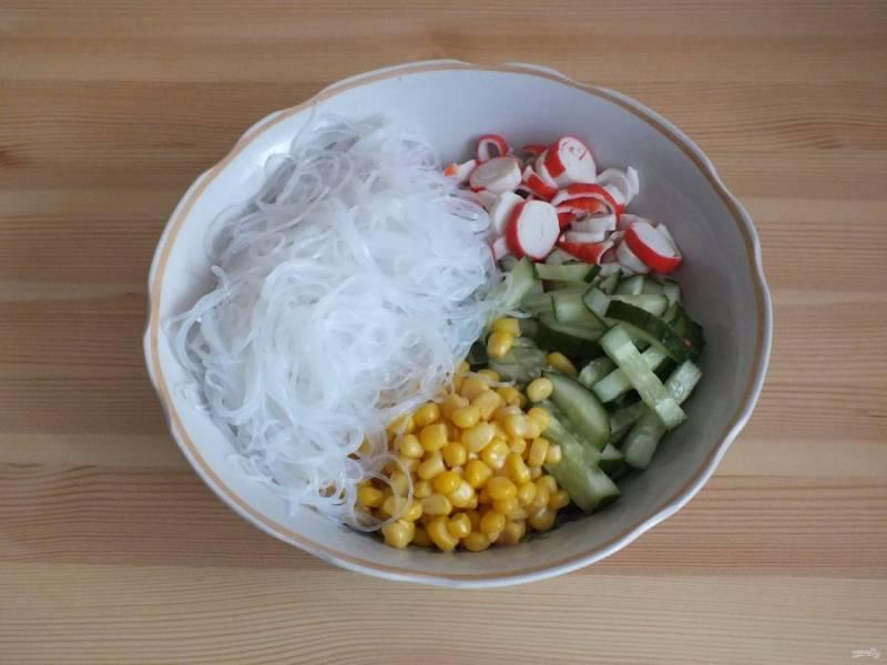 По истечении времени, откиньте фунчозу на дуршлаг и дайте хорошо стечь воде. Переложите в глубокий салатник. Добавьте к фунчозе огурец, кукурузу и крабовые палочки.