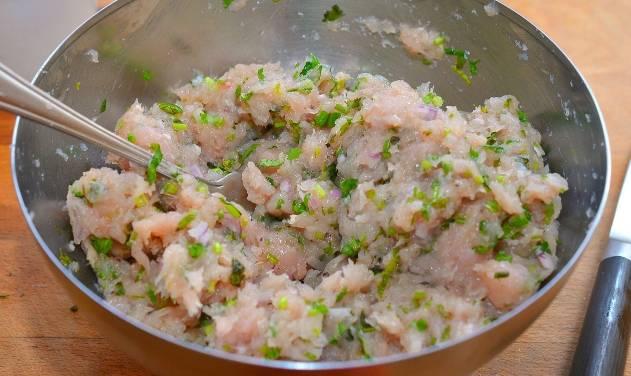 Смешайте куриный фарш с зеленью, мелко нарезанным луком и яйцом, посолите, поперчите.