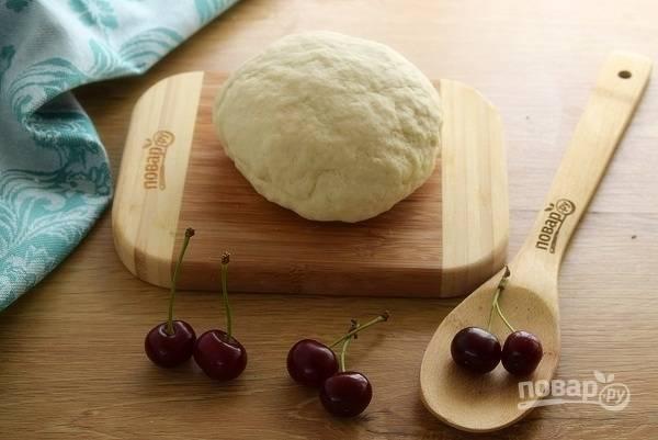 Муку и щепотку соли просейте в миску, в центре сделайте углубление. Влейте стакан сыворотки и замесите гладкое тесто. Накройте его пищевой пленкой и дайте набухнуть клейковине в течение 10 минут. В это время можно удалить косточки из вишни.