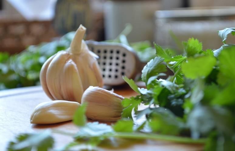 Как только картофель стал мягким, можно выключать огонь. Даем супу пару минут настояться под крышкой, а сами тем временем промываем свежую зелень и измельчаем ее вместе с чесноком.