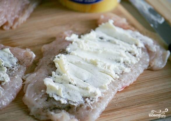 Куриное филе нужно нарезать на плоские широкие куски так, чтобы в них поместилась начинка. По необходимости отбиваем кусочки курицы. Солим и перчим. Берем творог или творожный сыр, намазываем его на каждый кусочек.