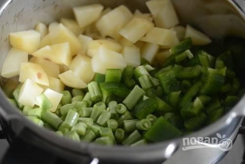 1. Очистите и нарежьте мелкими кубиками картофель. Нарежьте фасоль и соедините с картофелем в кастрюле или сотейнике.